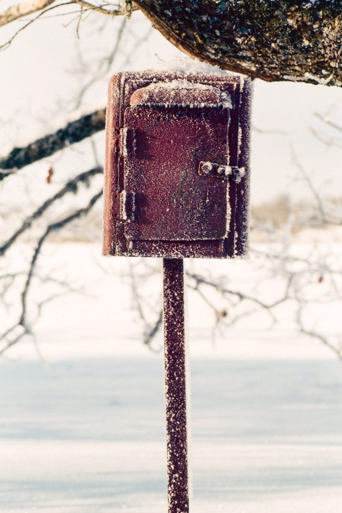 Photo of a post box in winter shot on slide film.