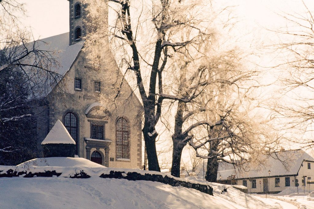 Photo of a church and some trees covered in sunlight taken on slide film.