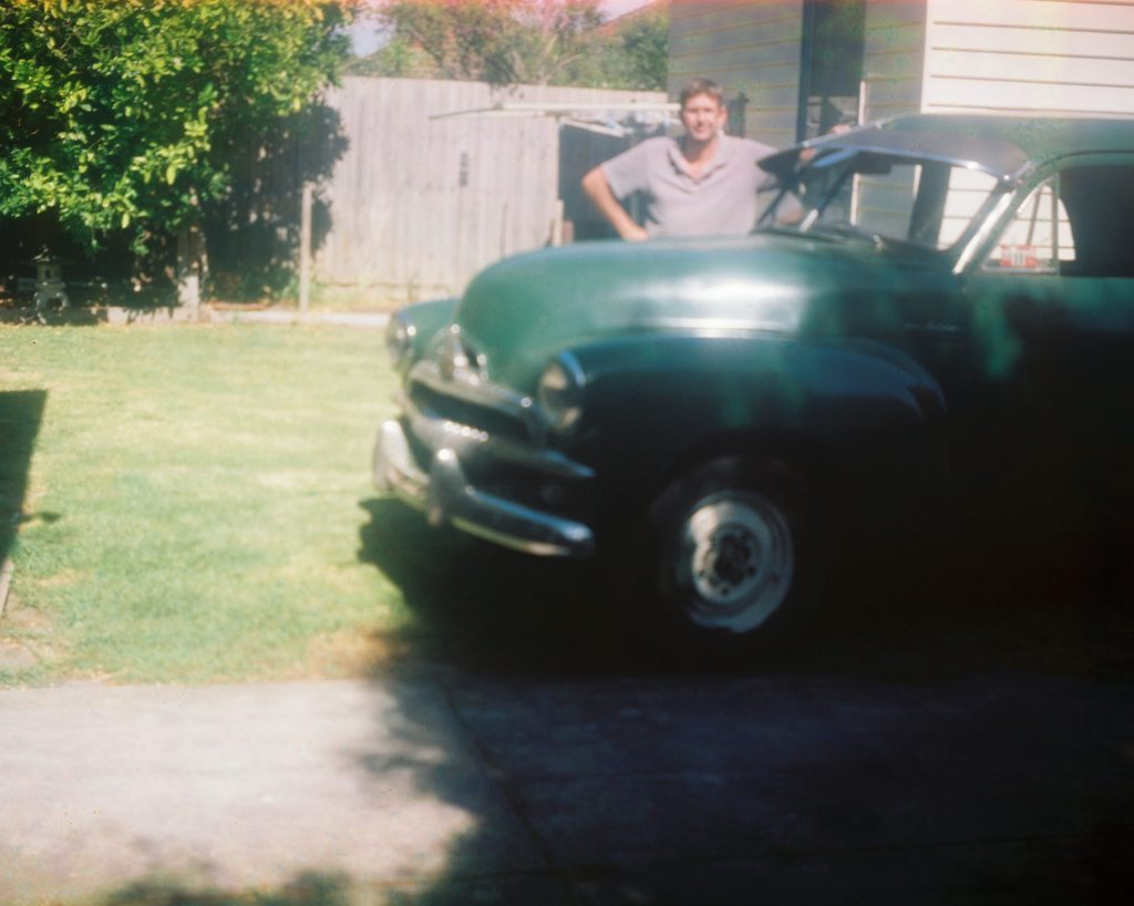 Green Holden FJ with person behind it