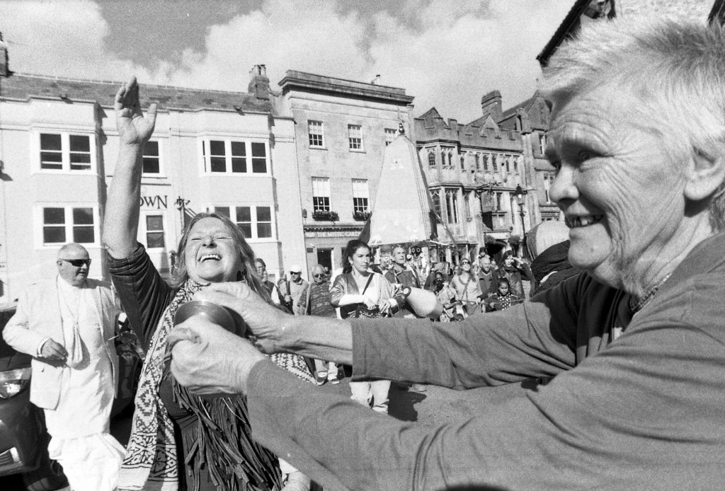 Devotees sing and dance through Glastonbury Highstreet, which itself is inundated with New Age shops.