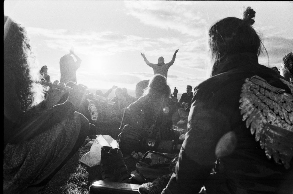 Devotees gather at the summit of Glastonbury Tor at sunset.