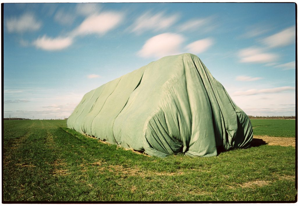 A long stack of straw bales under a green tarp stands on a field. Condensing time visible by many small white clouds that are passing overhead, smeared by the long exposure.