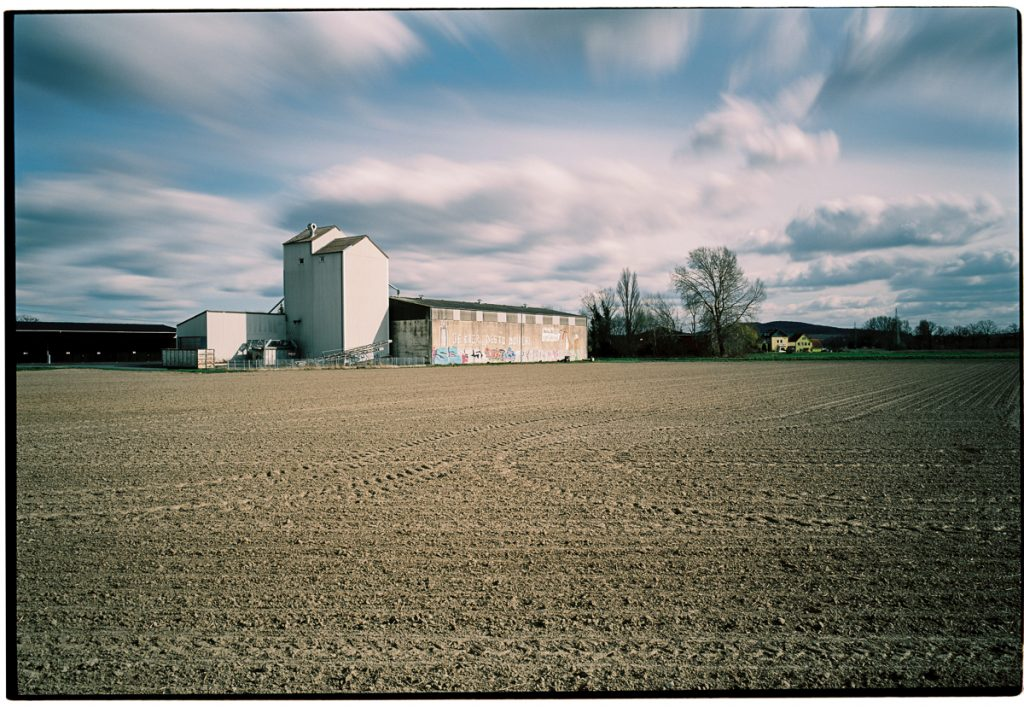 An agricultural warehouse is visible in the distance. Above the scene spans a dramatic sky; condensing time is again achieved by smeared clouds.