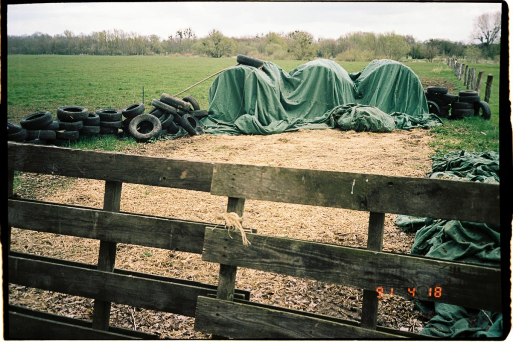 An empty pasture with a fence in the foreground and some straw bales under a tarp as well as some old tires in the distance.
