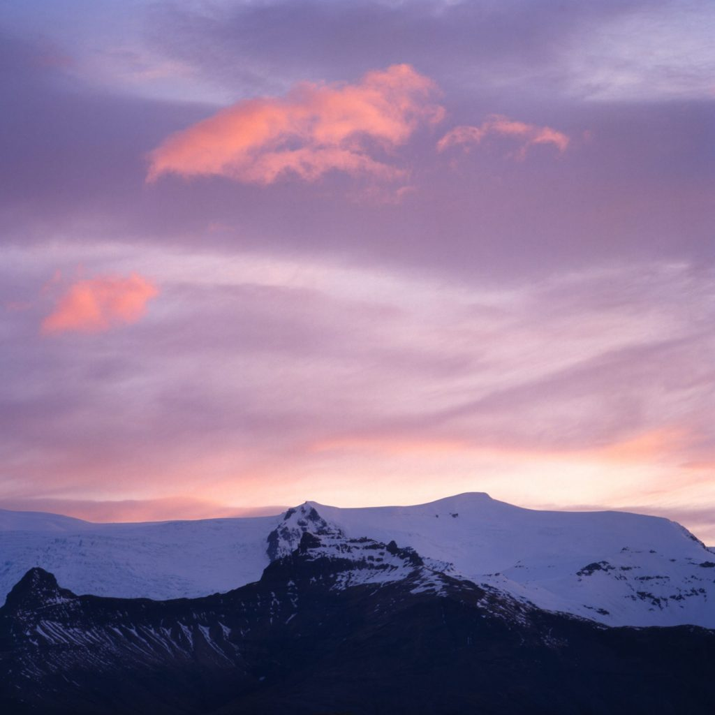 snow covered mountains and pink sky