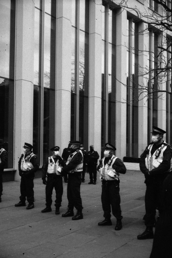 A line of police in front of an office building.