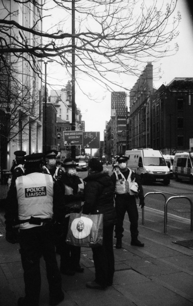 Police holding back a woman attempting to pass the line.