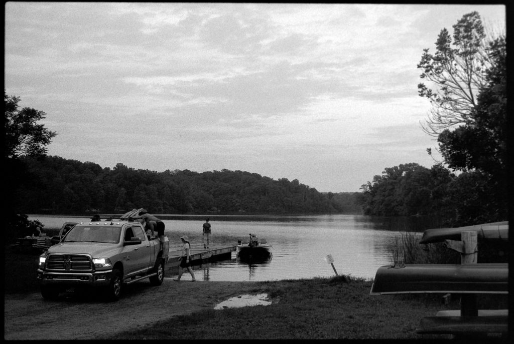 Family packing up jeep at the lake