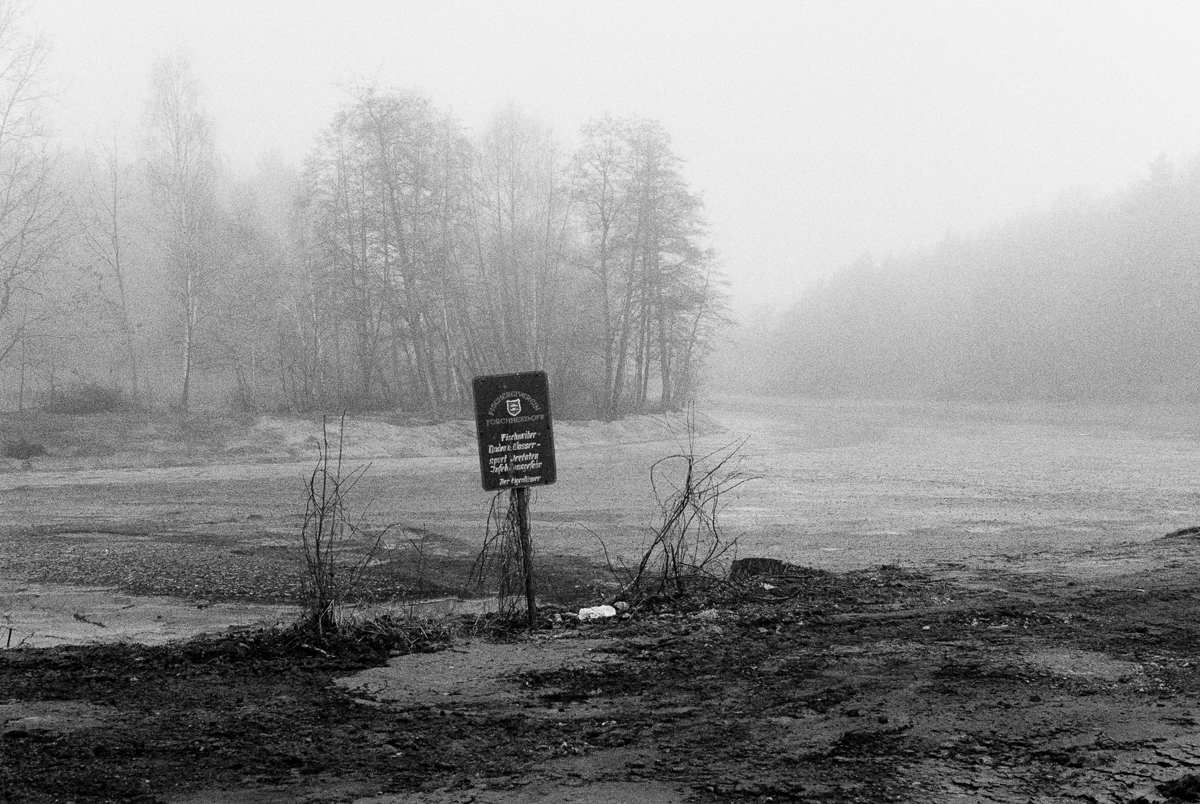 A drained pond in the morning haze.