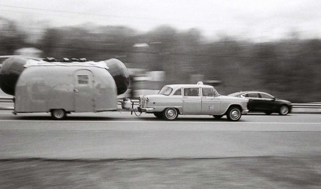 Car and Hot Dog trailer in traffic.