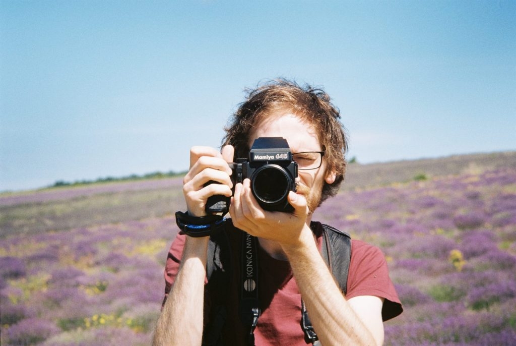 Portrait of a man taking a picture with his camera. Lavender fields in the background. Taken with a Voigtländer Bessamatic using a 90 mm lens and Kodak Gold 200