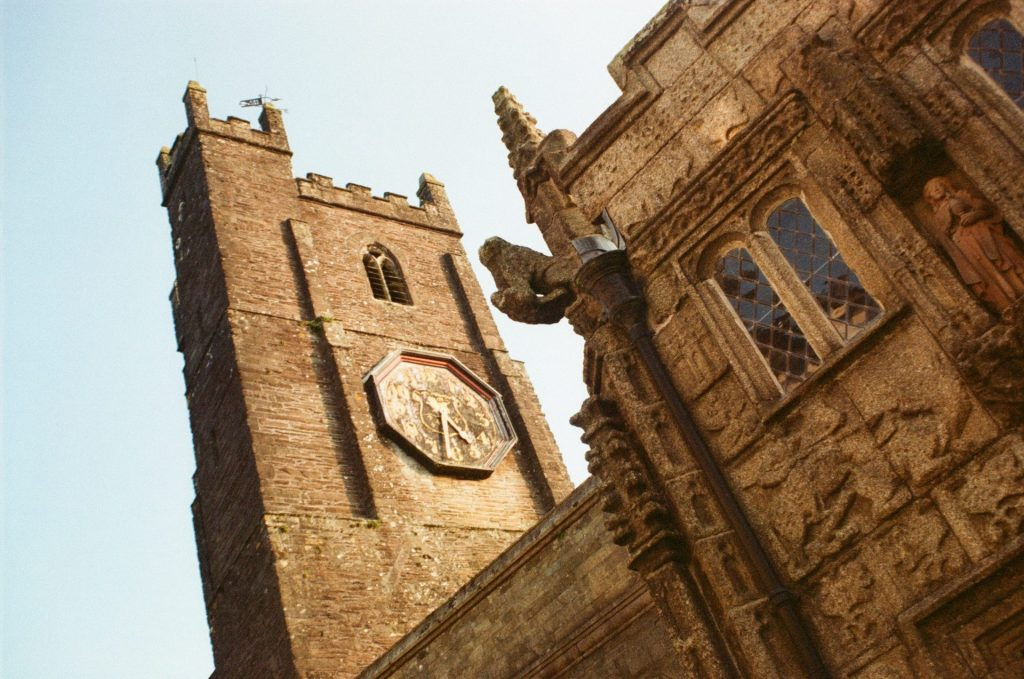 Carved granite church wall and clock tower
